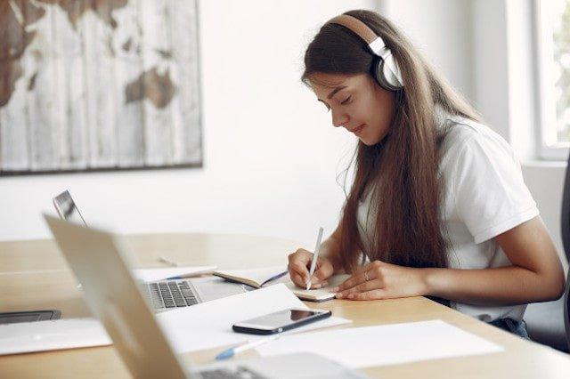 mlody-student-siedzi-przy-stole-i-korzysta-z-laptopa_